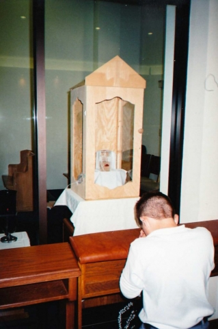 A boy praying in front of the Eucharistic Miracle of Dallas